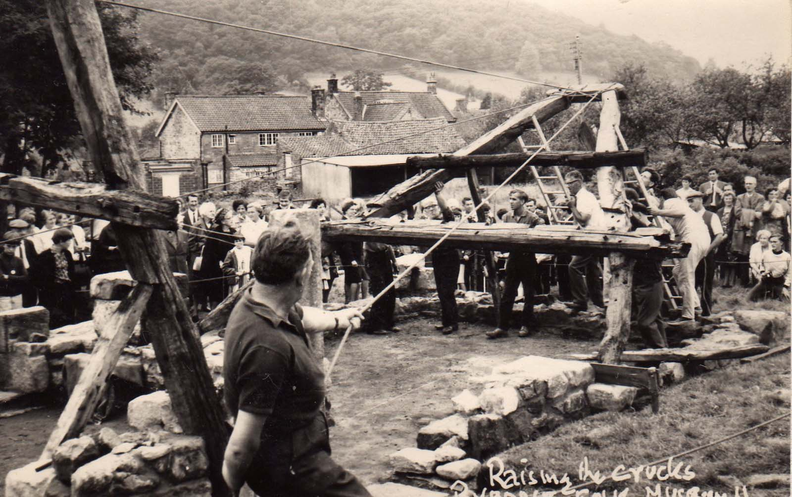 a black and white photo of people raising timber beams