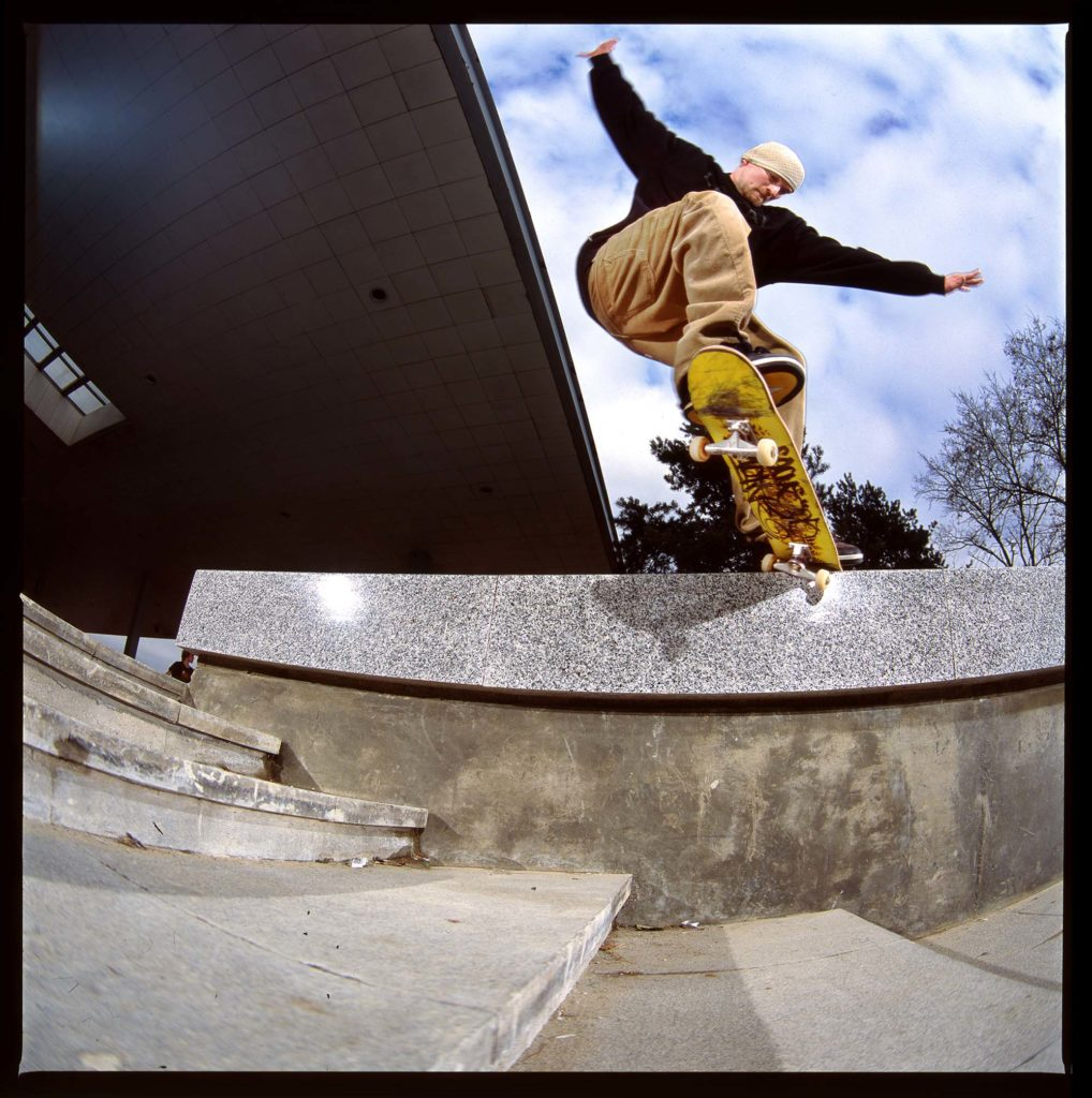 a photo of a skateboarder jumping over a concrete ledge