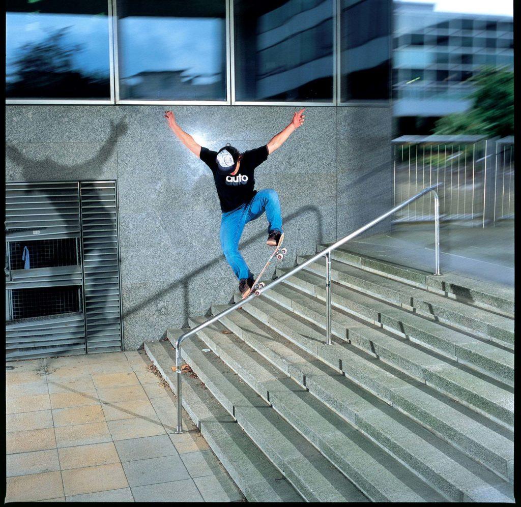 a photo of a skateboarder sliding down a railing
