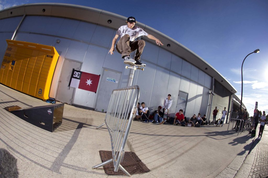a photo of a skateboarder ollying over a barrier