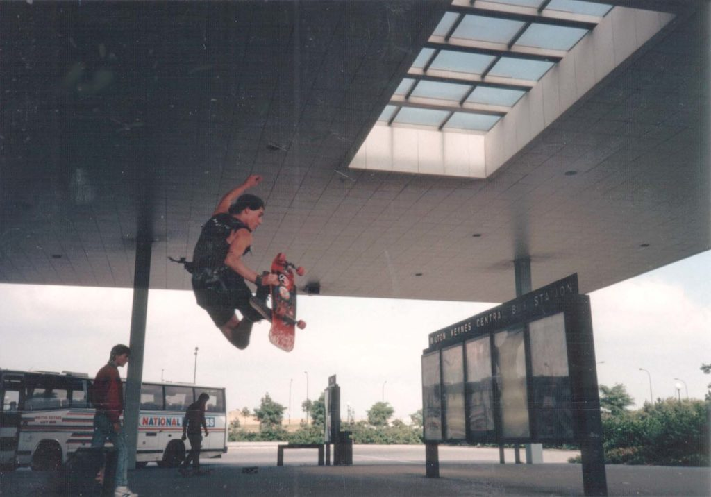 a photo of a skateboarder performing a trick at a bus station