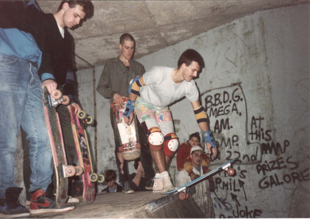 an old photo of a skateboarder about to drop in down a skate ramp