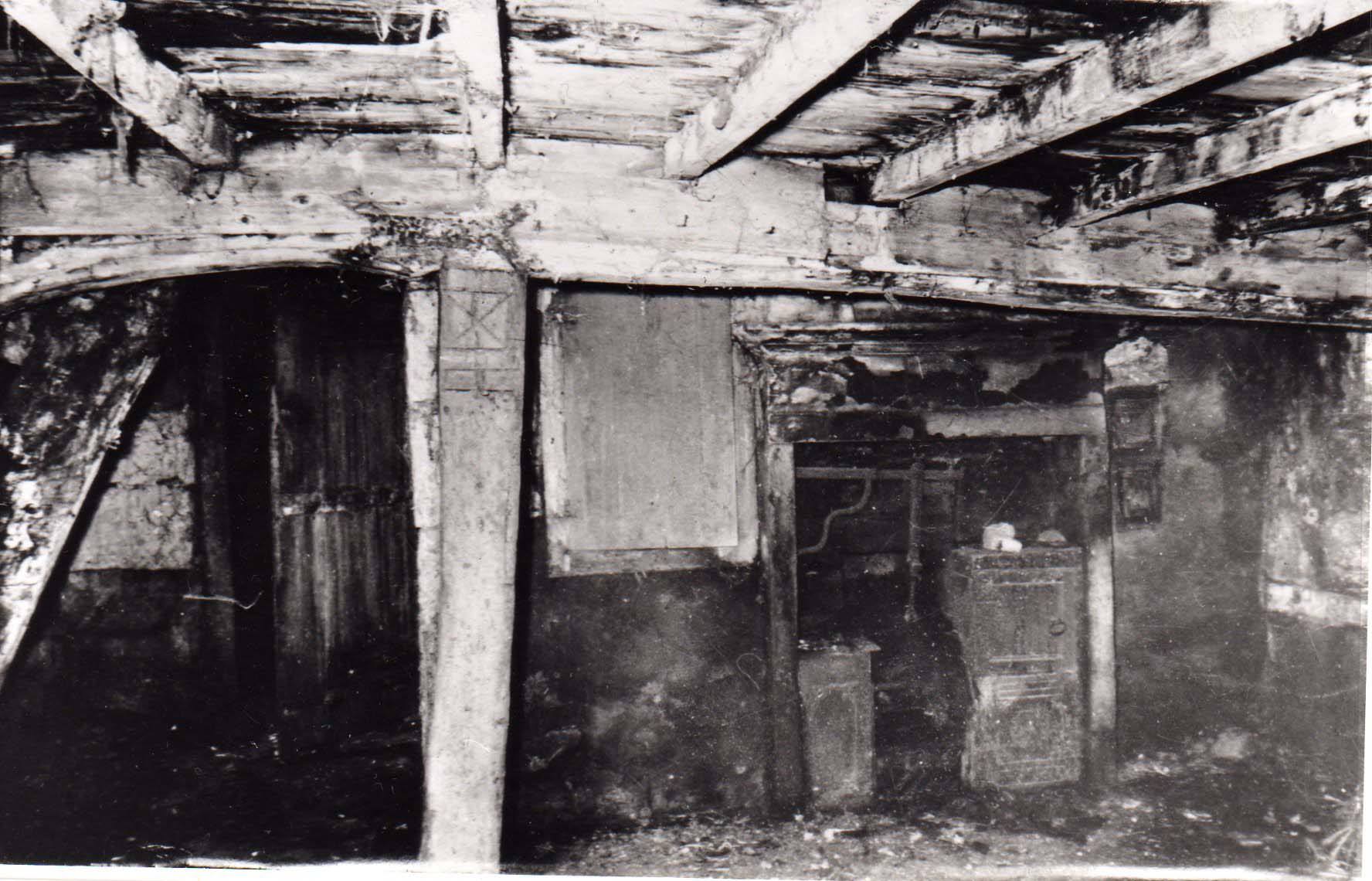 a black and white photo of a the exposed beams of a cottage