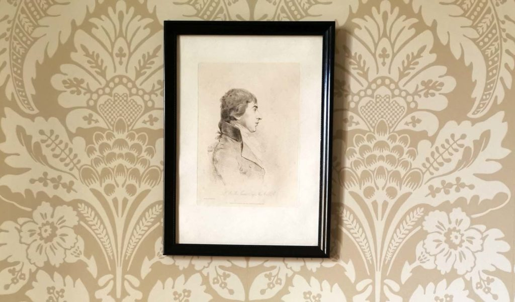 a photo of a portrait of Turner in side profile against gold floral patterned wallpaper
