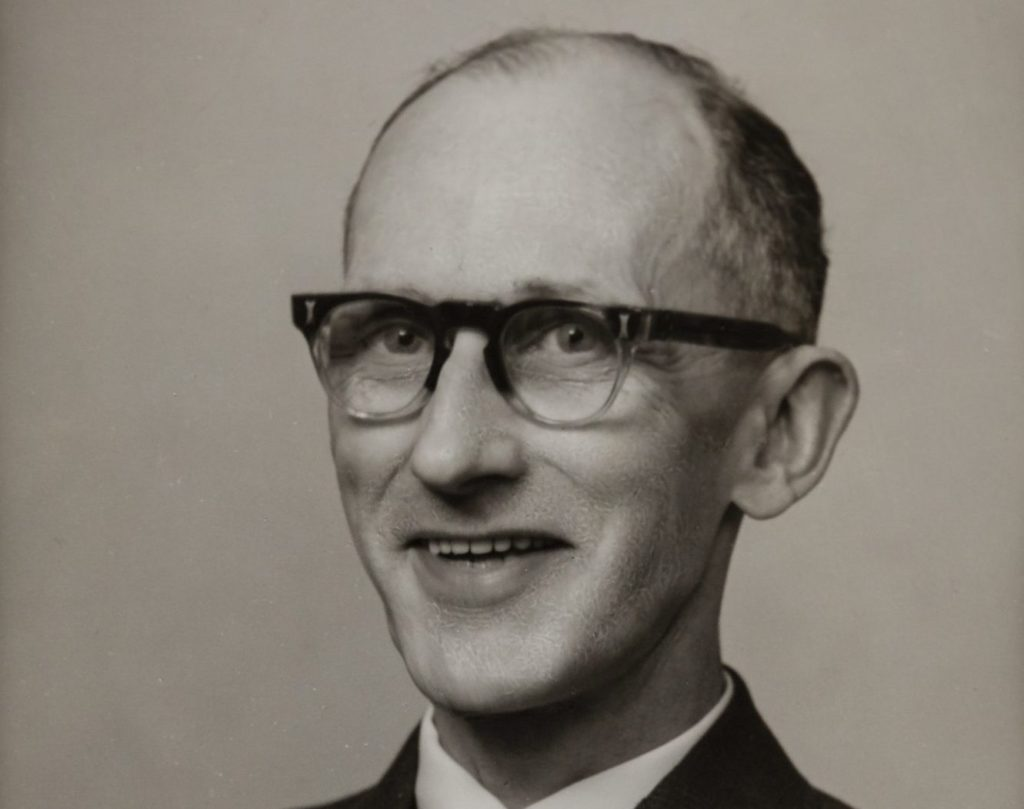 a head an shoulders black and white photo of a man wearing glasses
