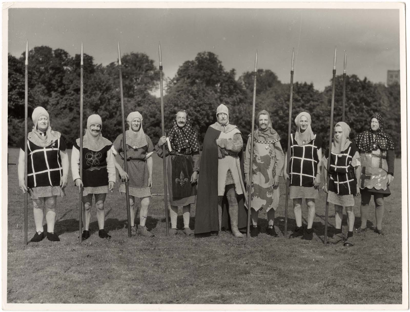 a black and white photo of a group of men dressed as medieval soldiers