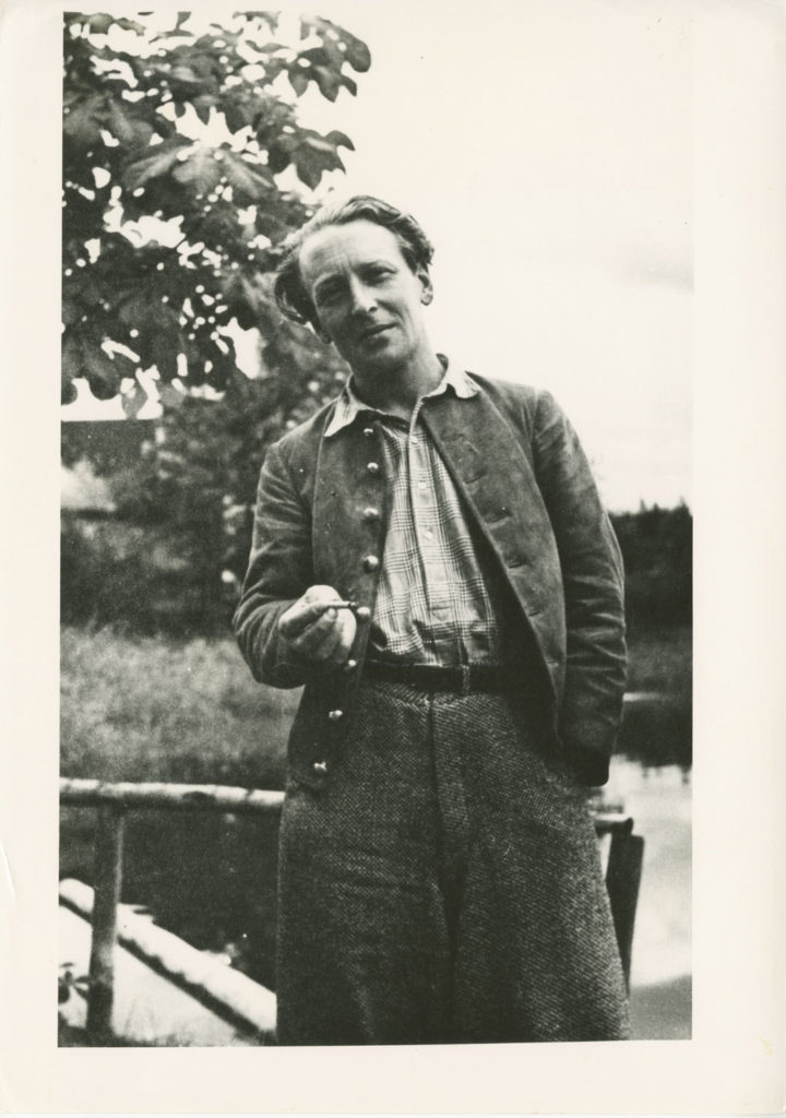 Tristram Hillier photographed in Germanic or Flemish style dress holding a cigarette
