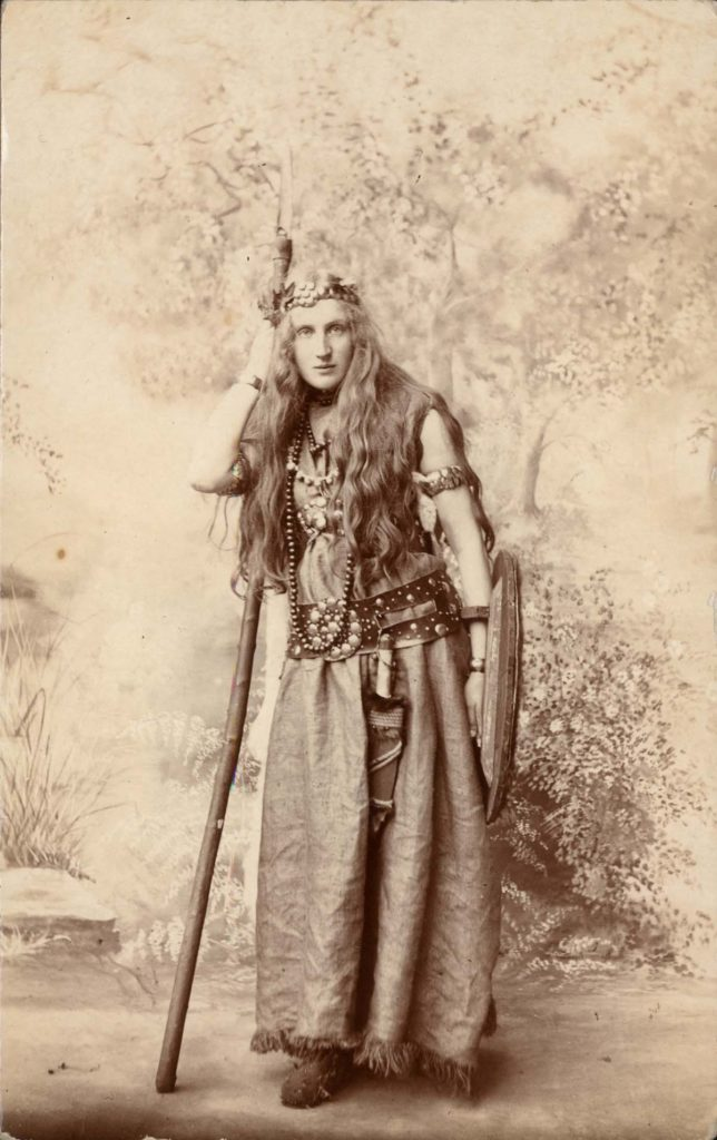 sepia full length studio photo of a woman with long hair, headdress, spear and shield