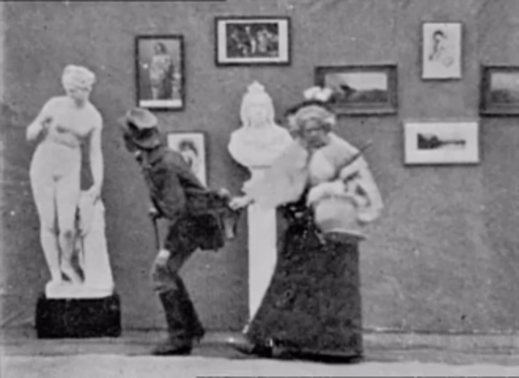 A film still showing a man looking at a nude statue, with a woman pulling him away