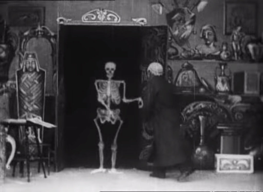 Film still showing man at a open cupboard being greeted by a skeleton