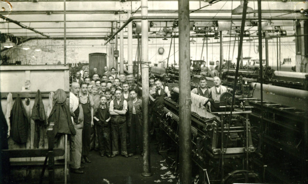 Men and boys in a factory room with large machinery
