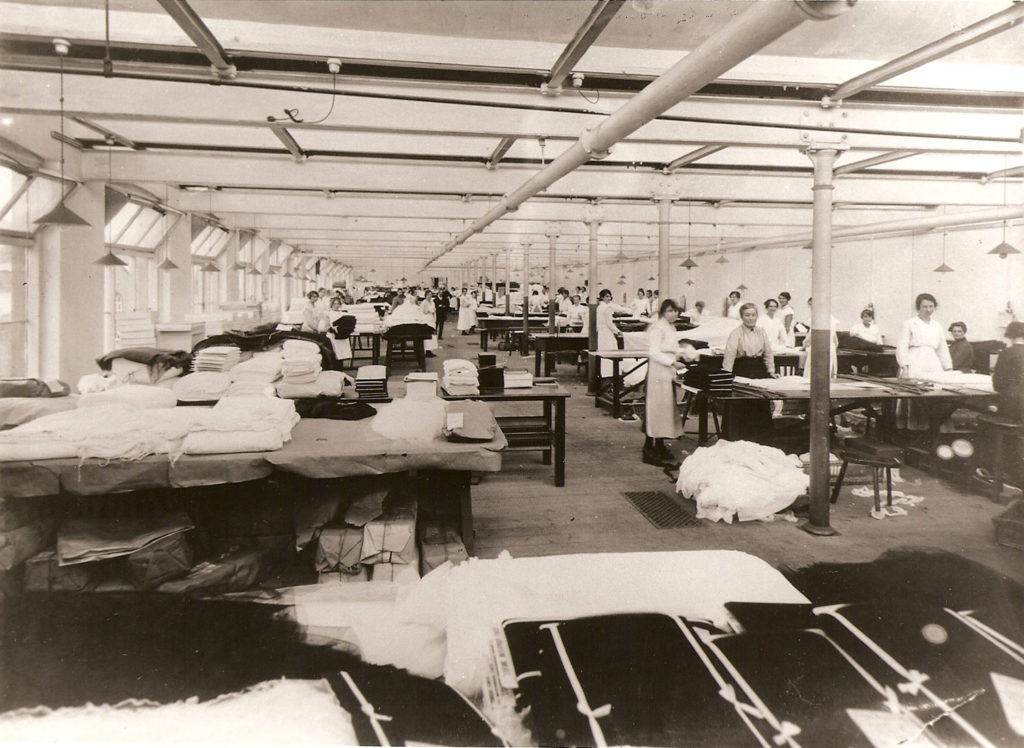 a factory floor with large tables covered in folded fabric, there are women standing at the tables