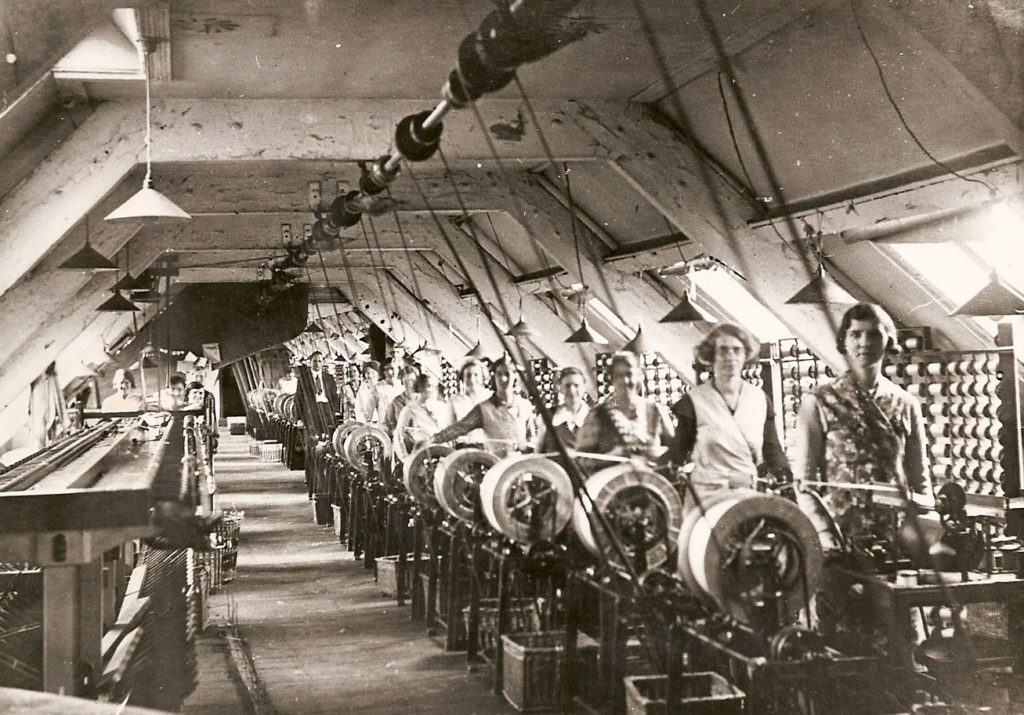 women standing by reeling machines in a factory