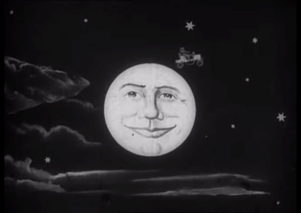 a film still showing cartoon moon with face in the night sky, a car can be seen driving away from it