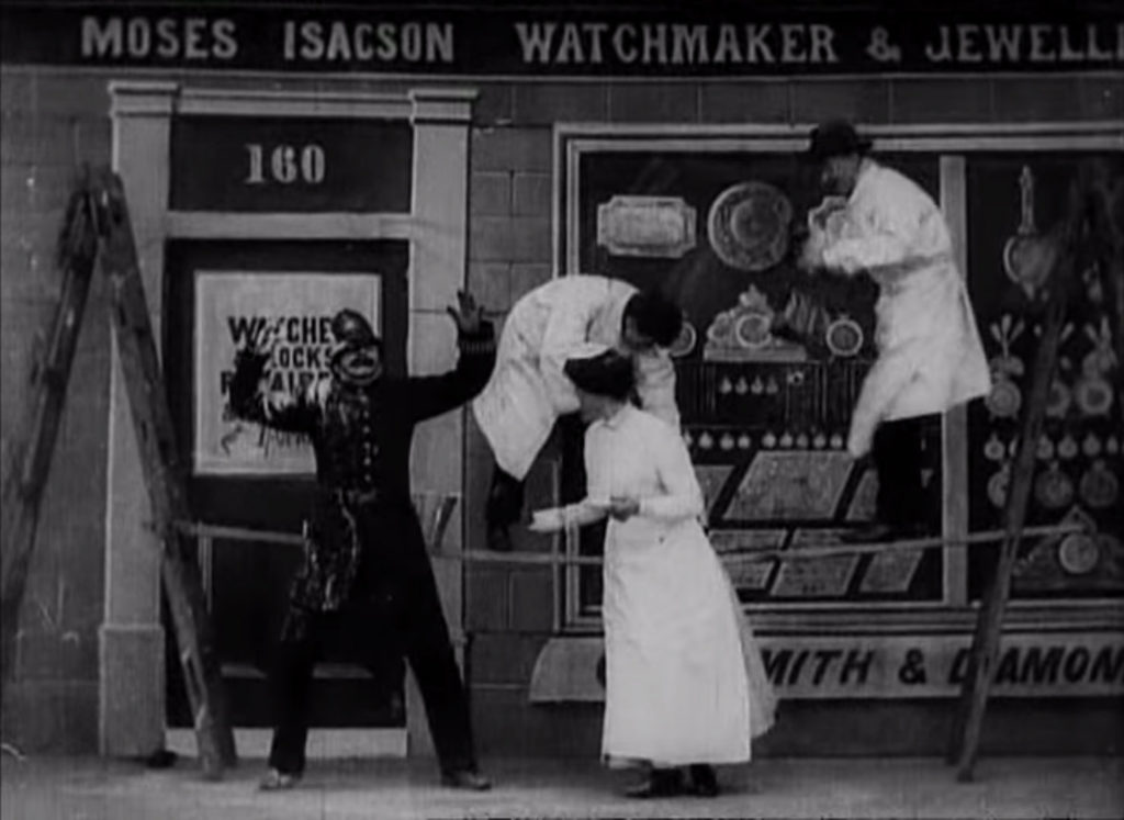 film still showing policeman covered in white paint in front of a pair of workmen on ladders