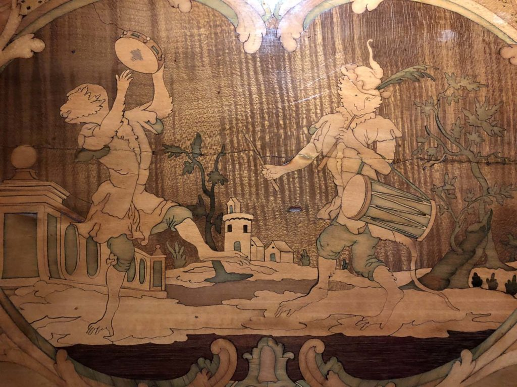 a wood inlay design depicting two men with drums