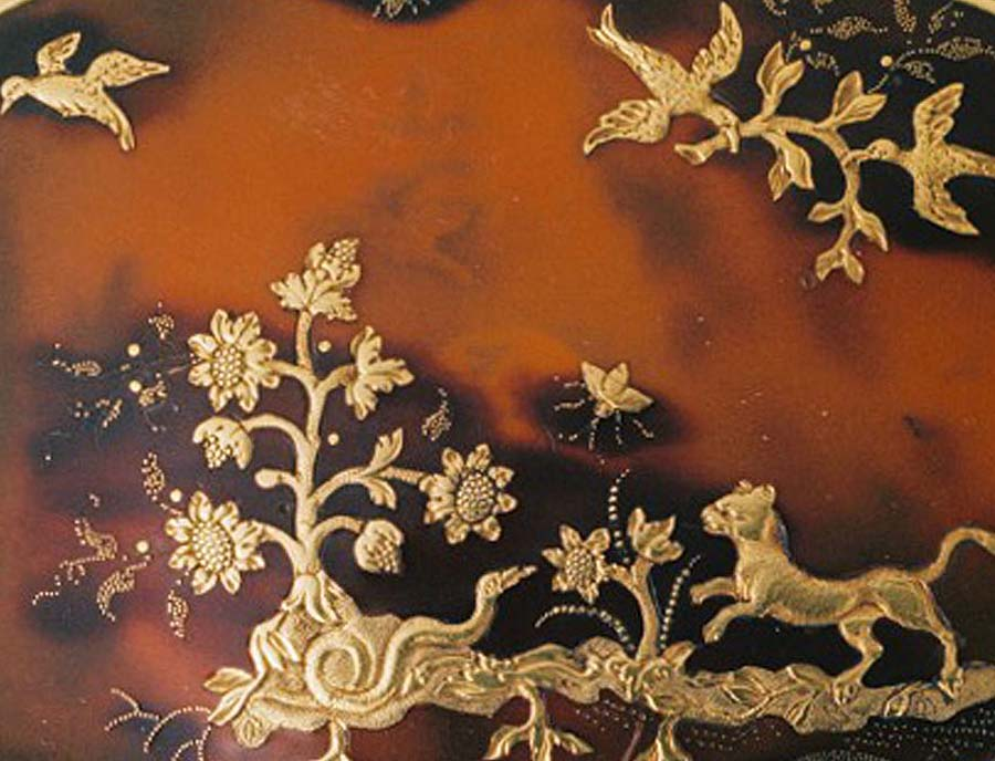 a detail of gold inlaid bird decoration on a snuff box