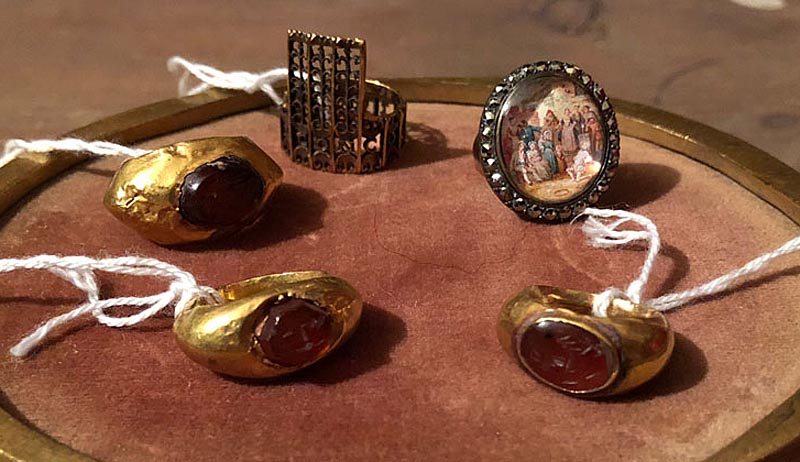 a photo of a five gold rings of various types, mainly with inlays