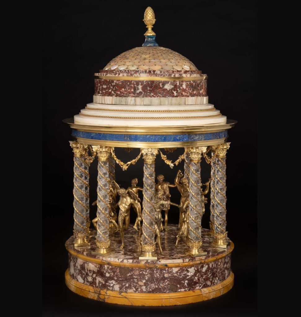 an onrate table decoration of a golden rotunda with golden ladies dancing inside it