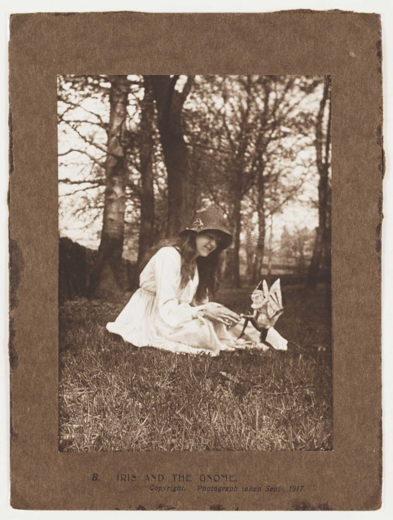 a black and white photo of a teenage girl sitting in the meadow with a cardboard cut out figure of a gnome