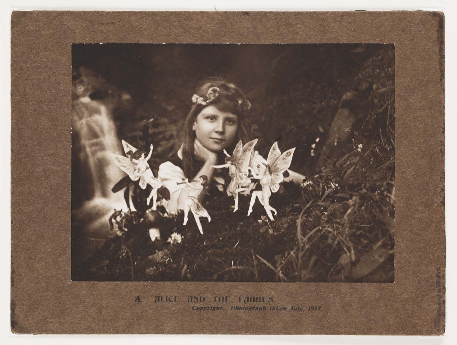 a black and white photo of a young girl with cut outs of fairies in front of her