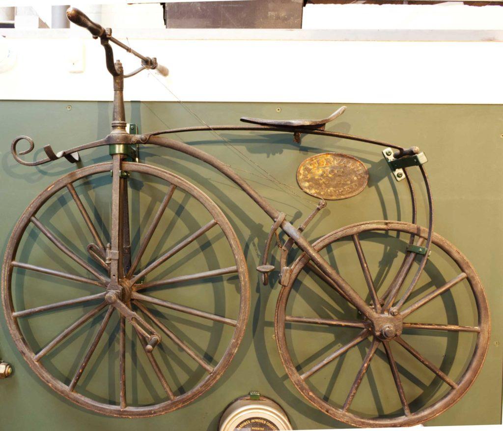 a photo of an old boneshaker bike mounted on a wall