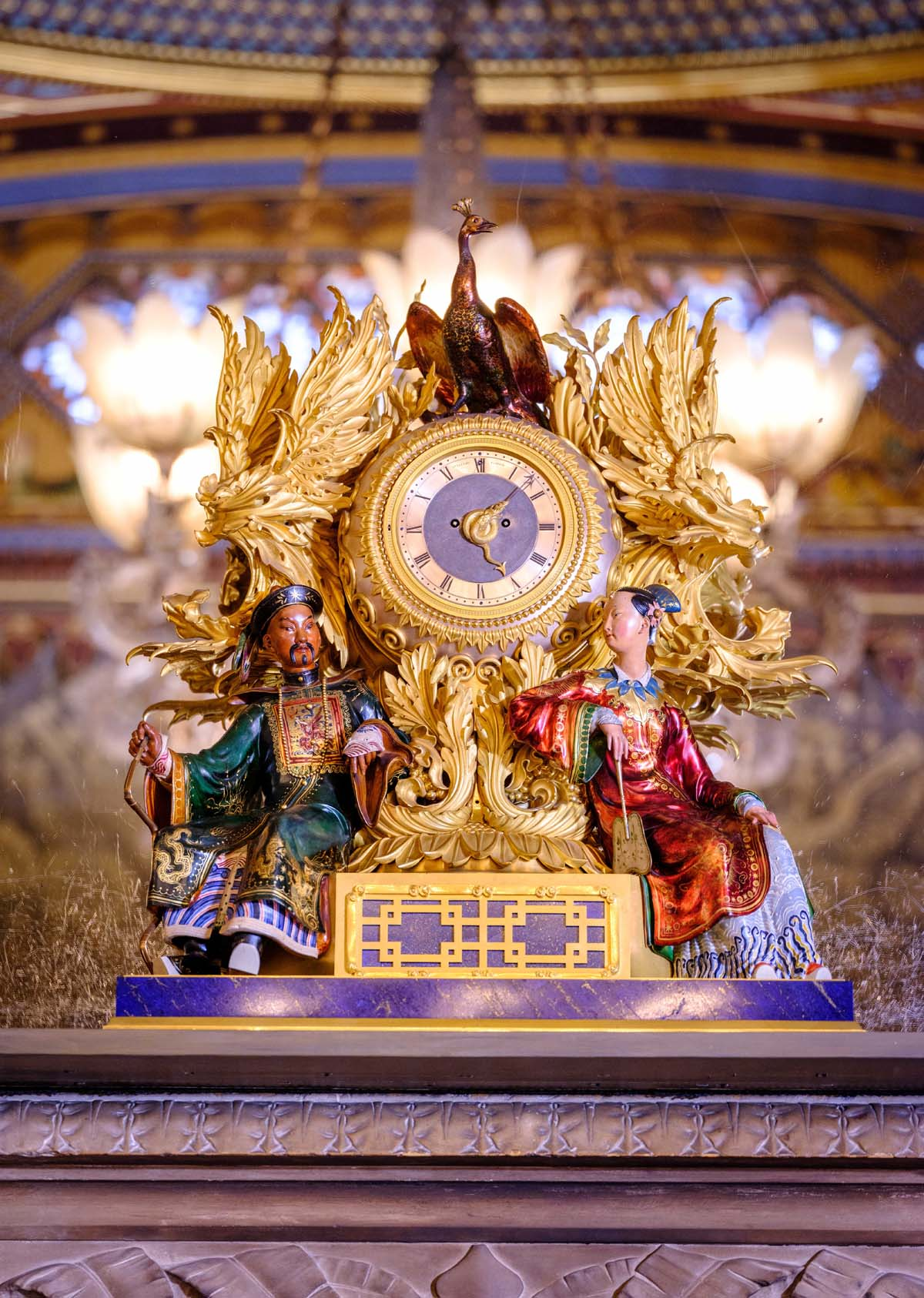 a photo of a gold clock with two chinese figures resting on either side of it