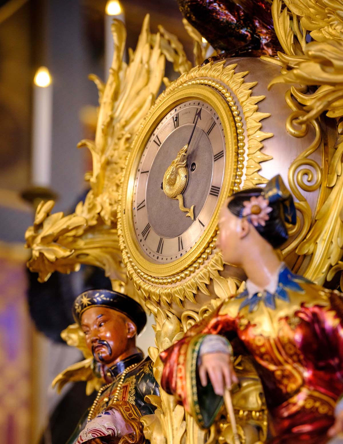a close up of two Chinese figures on a Chinoiserie clock