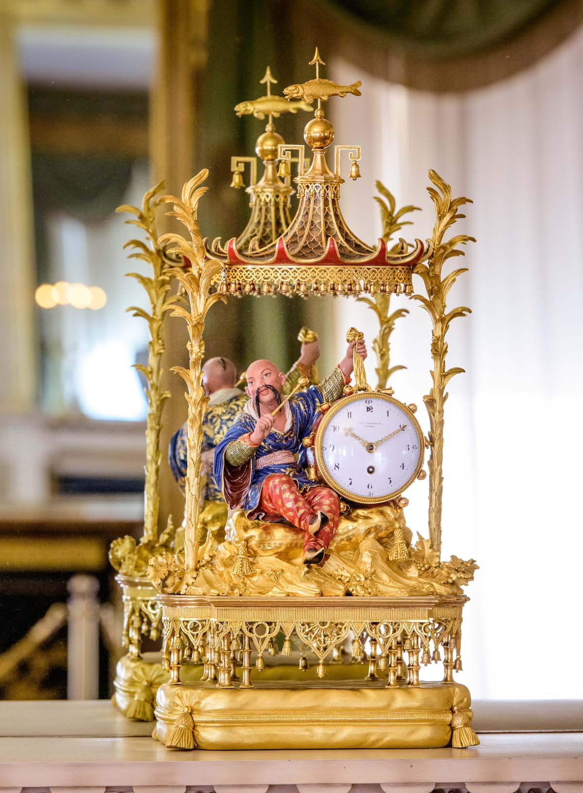 a photo of an ornate gold clock oin which a Chinese drummer figure beats the clock face