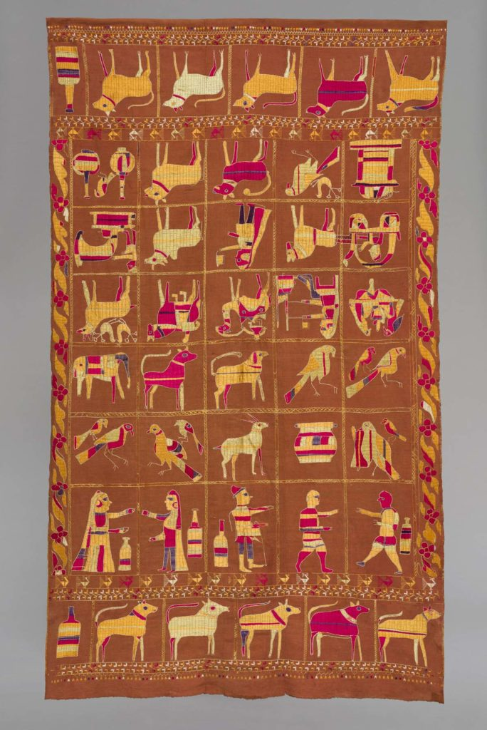 a photo of a hanging textile with people and animal figures on it