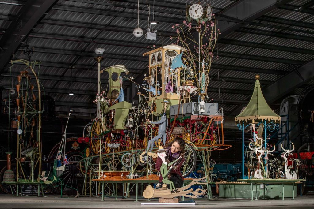 a photo of a large kinetic sculpture with a train, cows, and a man on a bicycle