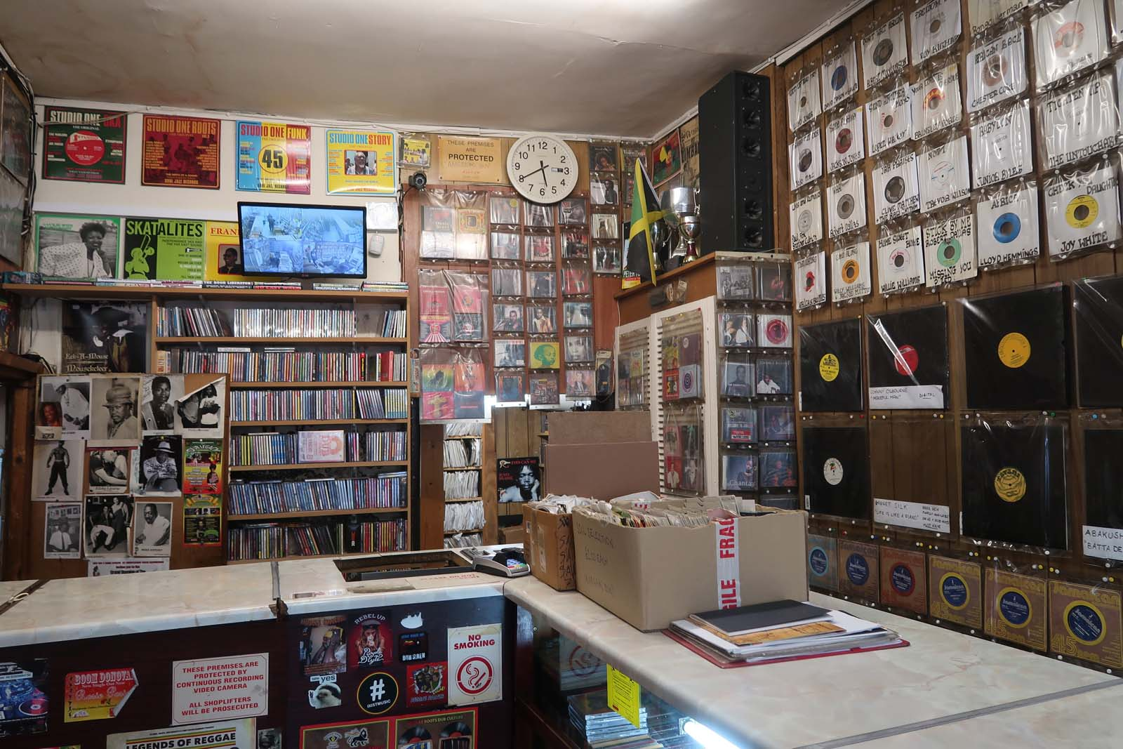 a photo of the interior of a record shop with counter and records sleeves on the walls behind