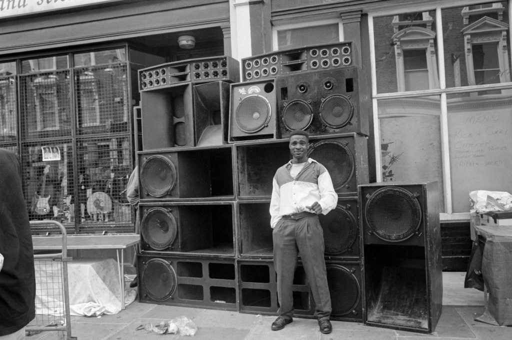 A man standing in front of a bank of loud speakers in All Saints Road, Notting Hill, during the Notting Hill Carnival, 21st August 1994. Photograph by Peter Marshall.