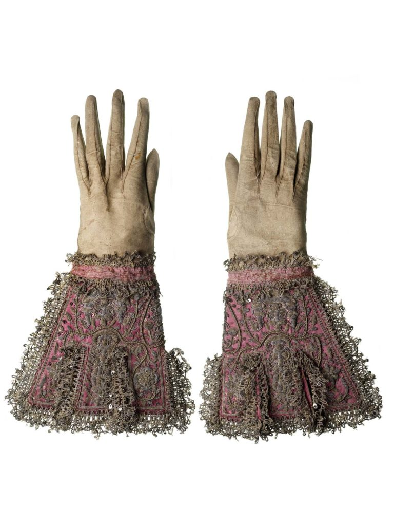 a pair of rich gloves, kid with suede side outward, fitted with deep gauntlet cuffs of pink silk, tabbed and trimmed with gold and silver lace and embroidery.