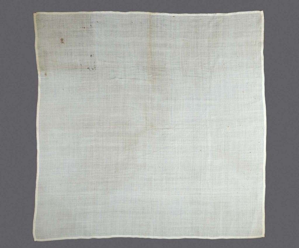 Square fine linen handkerchief embroidered in cross stitch with small red cipher 'CR' surmounted by the Tudor crown in one corner. Handkerchief is stained and has some deterioration along old fold lines. VERY FRAGILE.