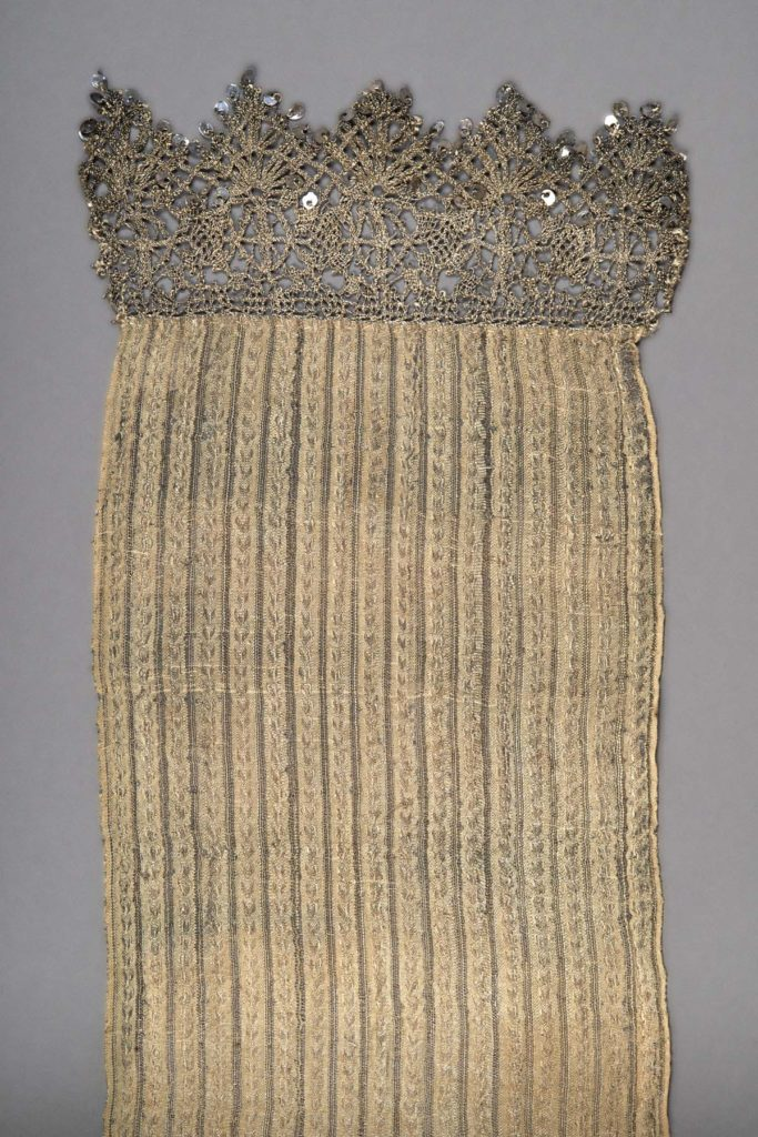 Silver-gilt fabric scarf or sash with silver-gilt lace and spangles. Woven as a wide ribbon with selvedges both sides. The warp is cream silk, and the weave is warp-faced. There are groups of 11 silver-gilt warp threads at regular intervals which are used to make a pattern of small vertical arrows in vertical stripes of about 20 warp threads. In between these rows are open net strips made from a warp of cream silk either side of a single metal thread. The entire weft is made from a very fine silver-gilt metal thread (metal wrapped around a white silk core, 0.1 mm diameter). The reflective quality shows through the warp-facing to give the whole length a subtle shimmer. The silver-gilt bobbin lace is worked form a thicker metal thread (0.4-0.5 mm diameter). L 68 3/4 inches, W 6 1/2 inches, lace 2 5/8 inches