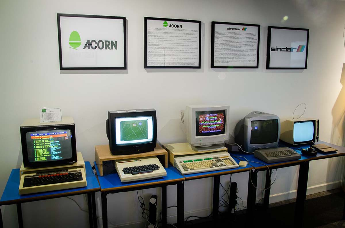 a photo of a room with four old computers on a table