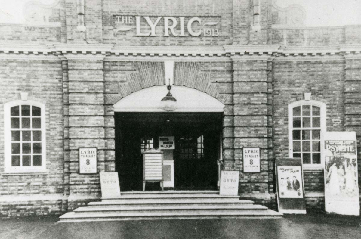 a photo of a cinema frontage with step leading up to a wide arched doorway