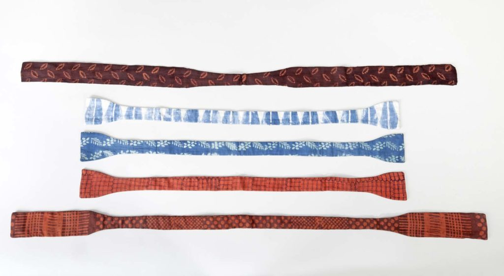 a photo of a series of ties laid out against a white background