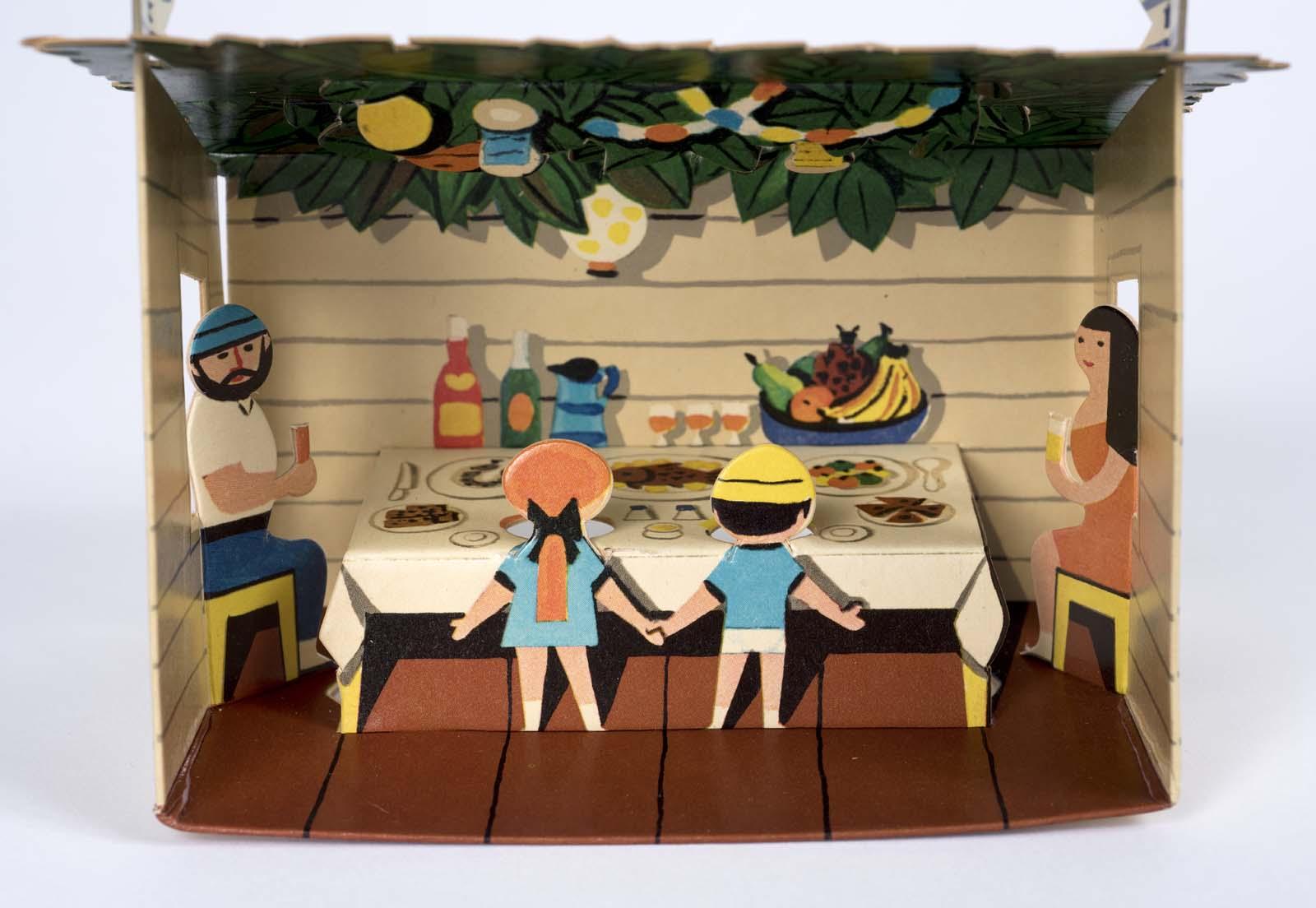 a cardbaord diorama showing a family eating a feast