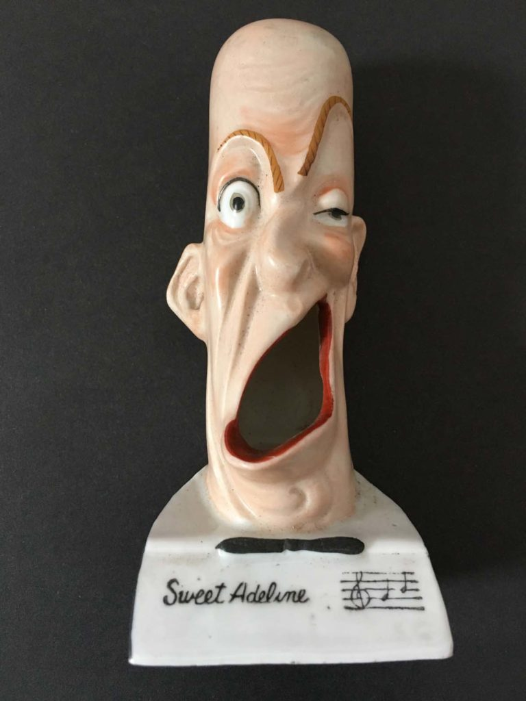 a porcelain face contorted in a strange grimace with an open mouth