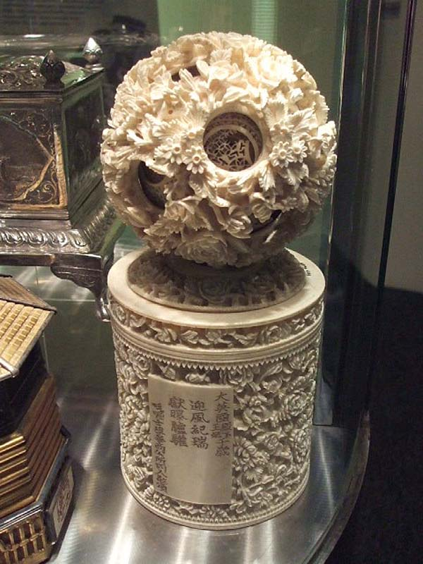 an ornately carved sphere made of layers of ivory mounted on an ivory tower