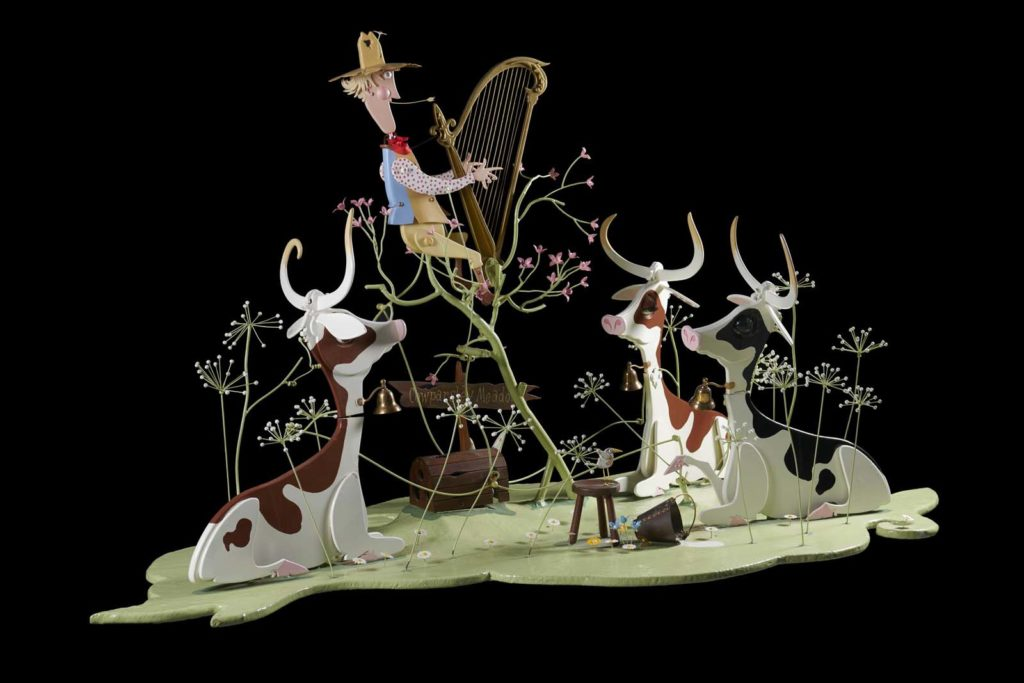a kinetic sculpture of cows in a field with a cow hand