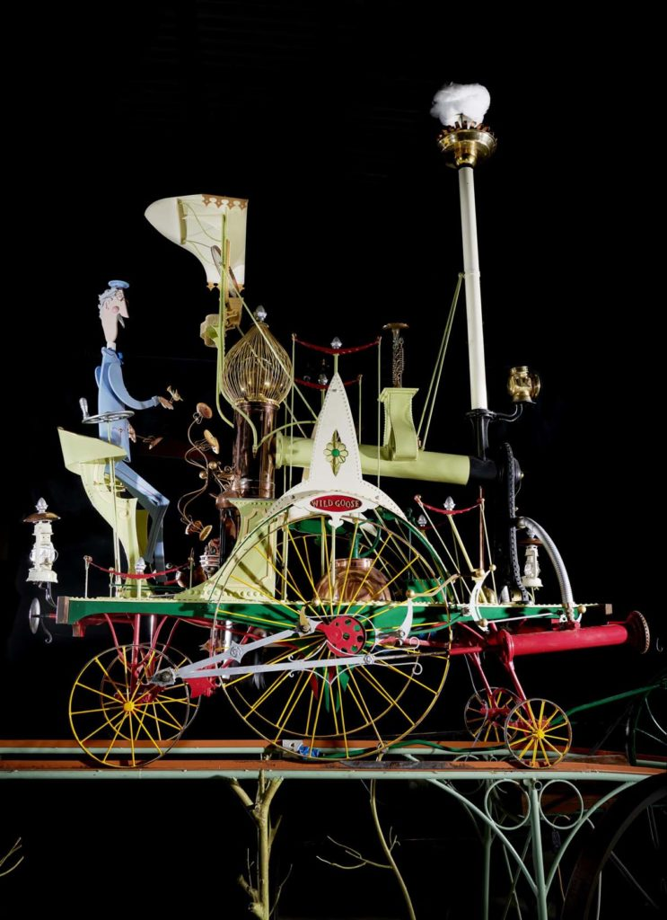 a photo of an automata with a man on a steam engine