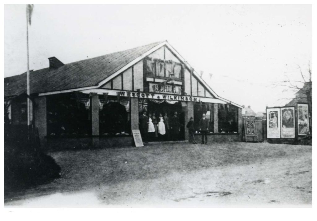 a photo of an old apex roofed building with Scala ciname sign and bunting outside