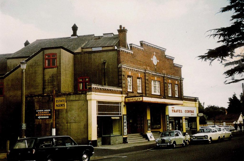 an old colour photo of a cinema called the waverley with 1960s cars parked in front
