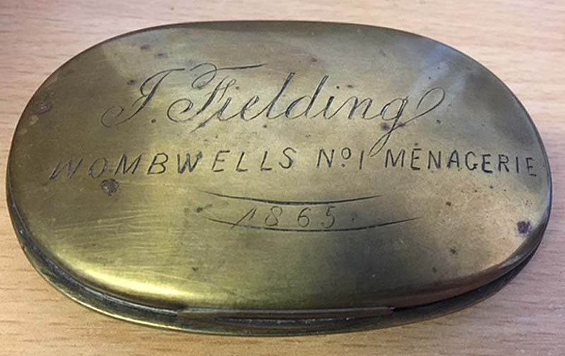 an oval tin with J Fielding Wombwell's No.1 Menagerie engraved on it