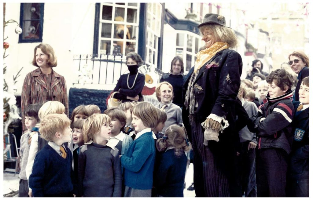 a photo of a man dressed as a scarecrow with a bunch of schoolchildren