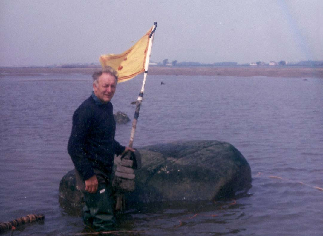 an old balck and white photo of a man stading next to a stone in a river with a Scottish flag