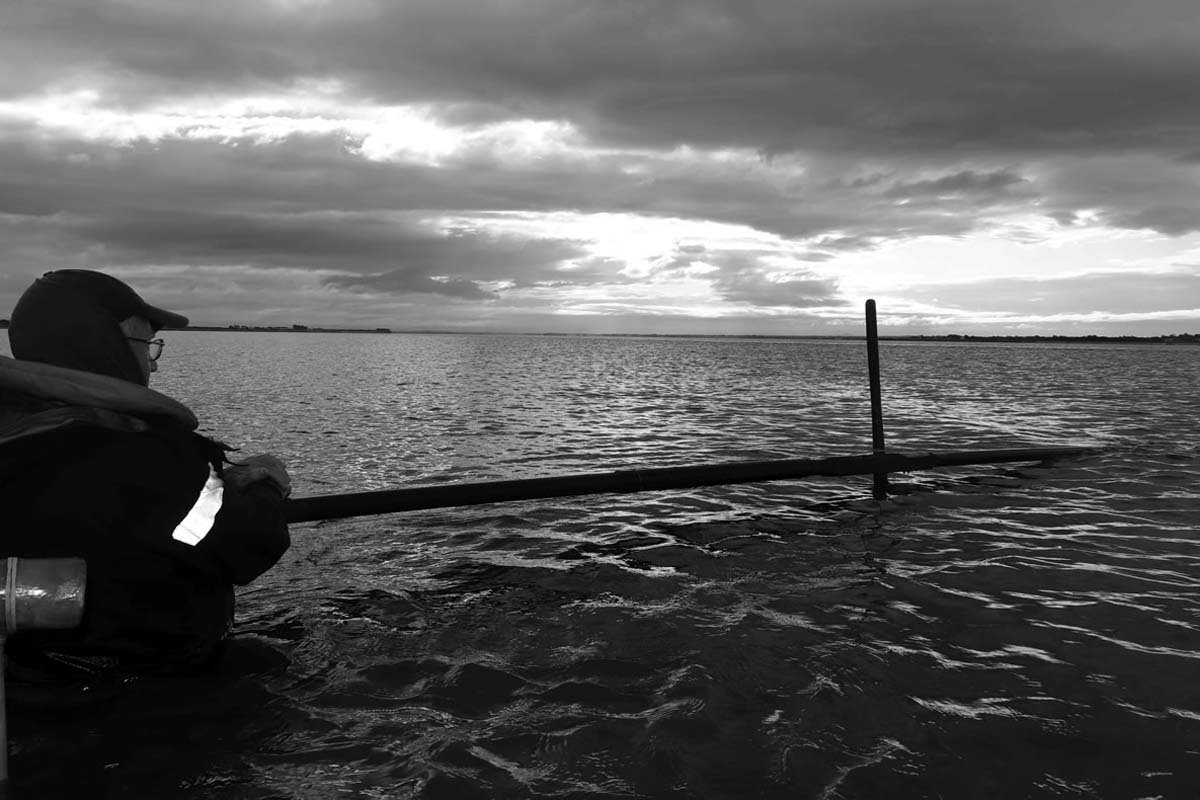a black and white photo of a man standing in a river holding a large net attached to a pole